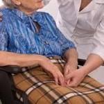 una donna anziana in carrozzina affiancata da un'infermiera